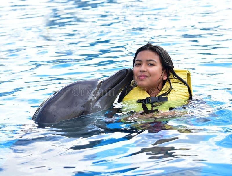 Ребенок целуя дельфина в бассейне стоковое изображение