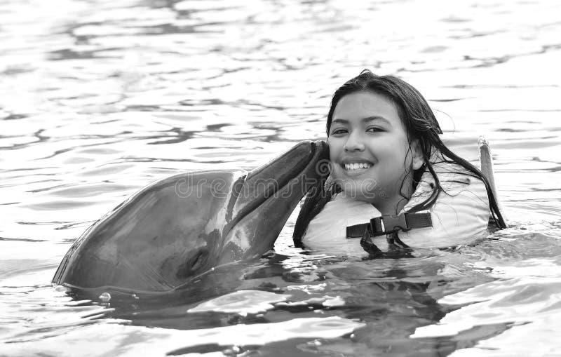 Ребенок целуя дельфина в бассейне стоковые изображения