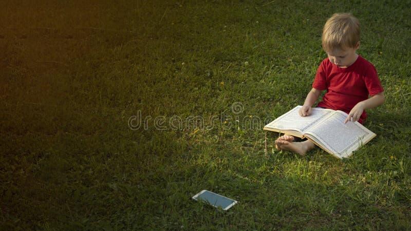 Ребенок читает книгу пока сидеть на траве, и его лож мобильного телефона рядом с ним повернул  Концепция образования и стоковая фотография rf