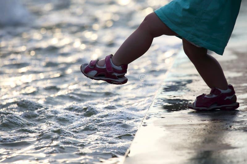 ребенок шагает в воду стоковая фотография