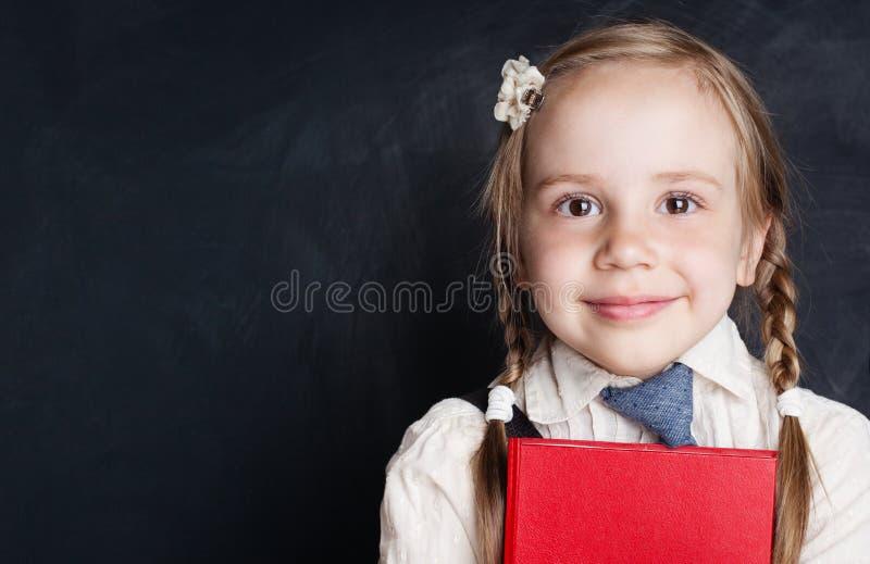 Ребенок школьного возраста с книгой на предпосылке доски мела стоковые фото