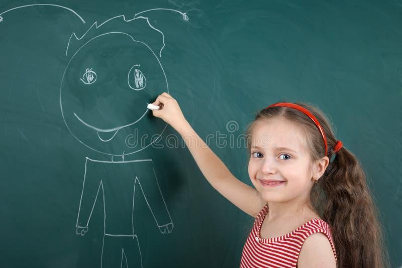 Ребенок школьницы в красном striped платье рисуя счастливого человека на зеленой предпосылке доски, концепции школьных каникулов  стоковое изображение