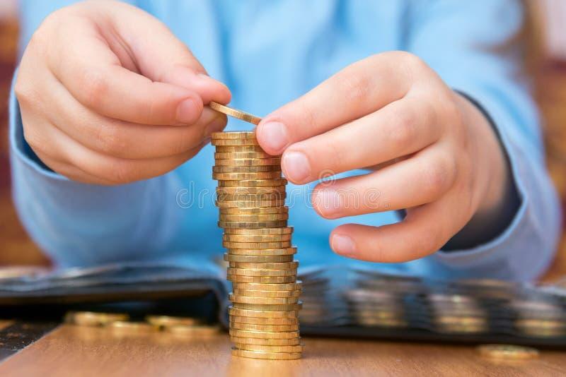 Ребенок amassed большая куча золотых монеток, конец-вверх стоковые изображения