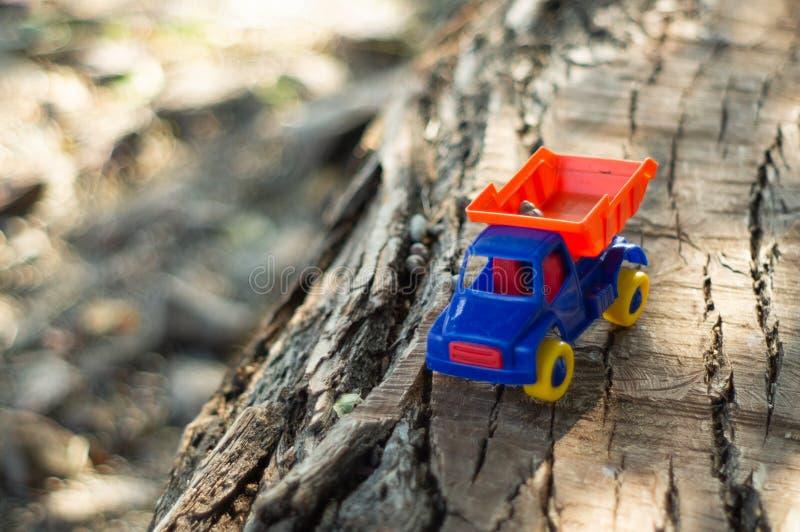 ребенок outdoors играя Ребенк мы льем песок в красную тележку Мальчик игр a улицы детей играя с машиной на большом журнале стоковое фото rf