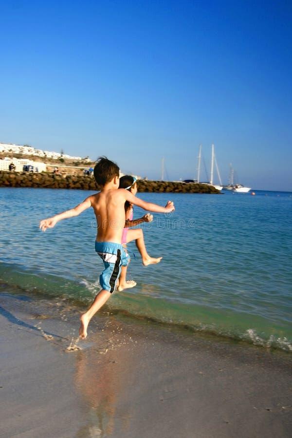 ребеята потехи пляжа участвуют в гонке к стоковое изображение
