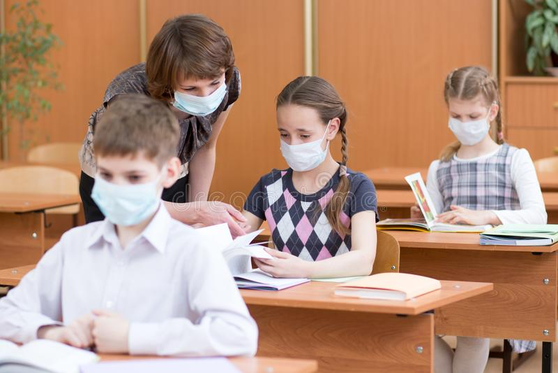 Ребеята школьного возраста с масками защиты против вируса гриппа на уроке стоковое изображение