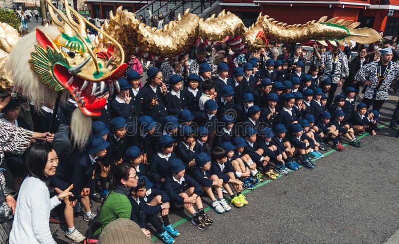 Ребеята школьного возраста на золотом танце дракона в токио стоковое изображение rf