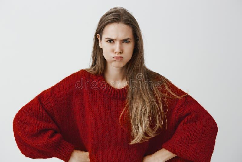 Ребяческая подруга хочет внимание Портрет раздражанной обиденной европейской женщины в красном свободном свитере, держа руки стоковые фотографии rf