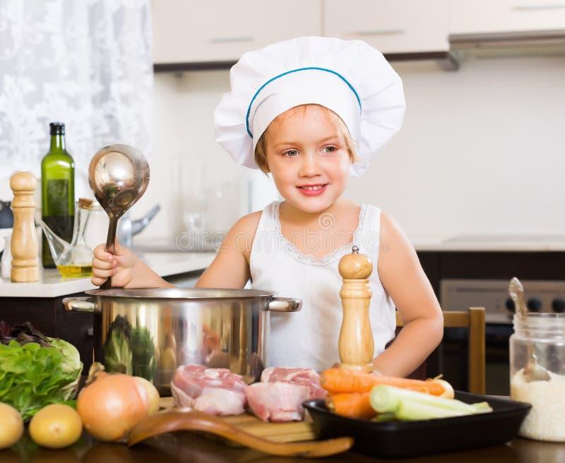 Ребёнок варя суп с ковшом стоковые фото