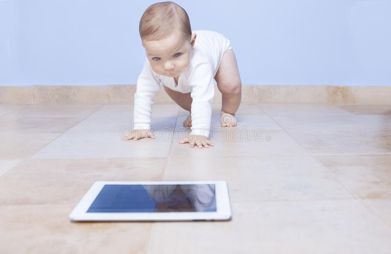 Ребёнок вползая к таблетке стоковое фото