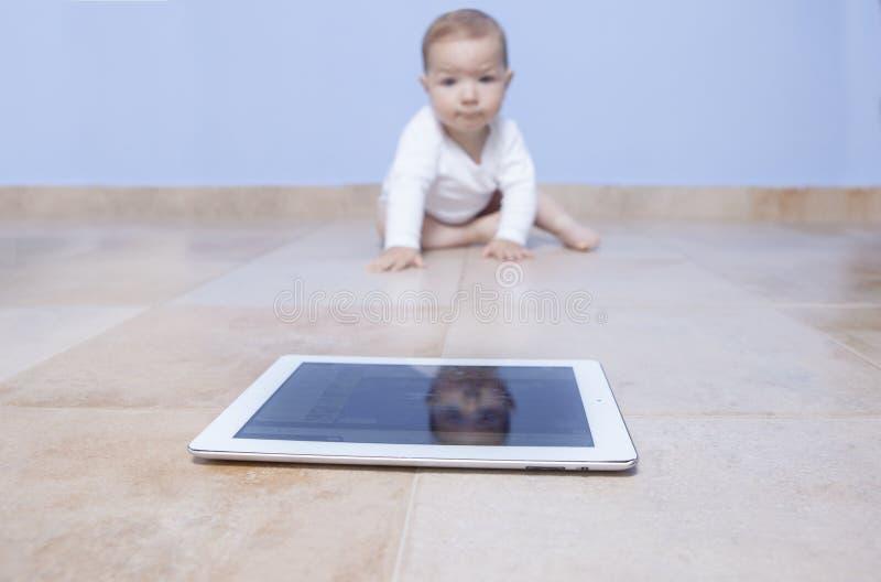 Ребёнок вползая к таблетке стоковое фото rf