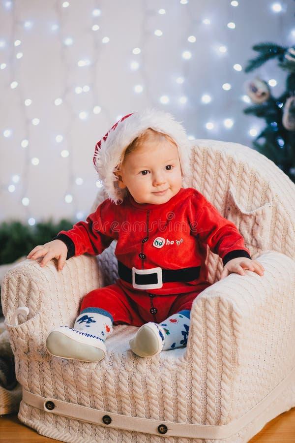Ребёнок в костюме Санта Клауса сидя под рождественской елкой стоковые изображения rf