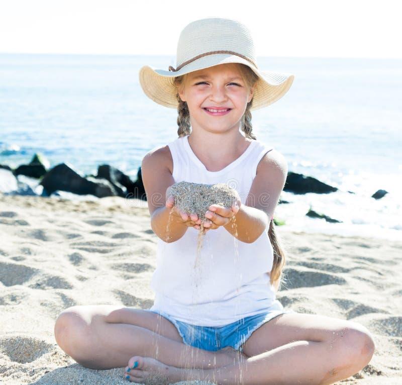Ребёнок в шляпе играя с песком на морском побережье в лете стоковые изображения