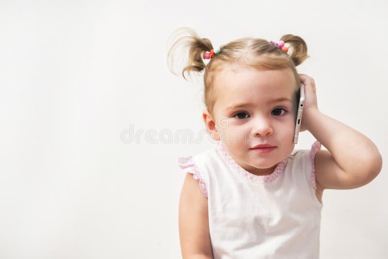 Ребёнок говоря сотовым телефоном, белой предпосылкой стоковые фотографии rf