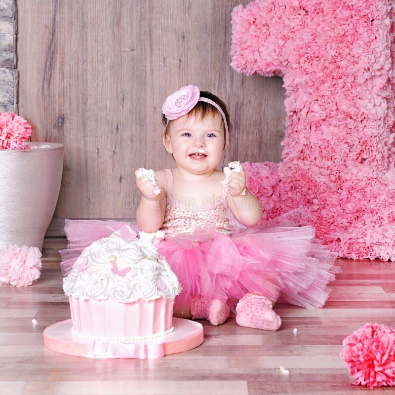 ребёнок 1 года в розовом платье с ее первым именниным пирогом стоковое изображение