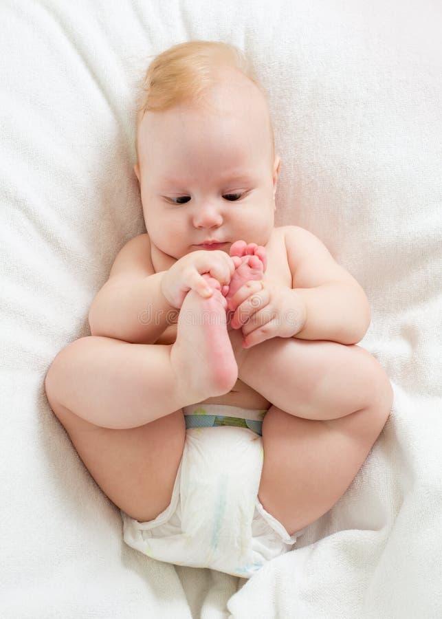 Ребёнок лежа на кровати и держа его ноги стоковая фотография rf