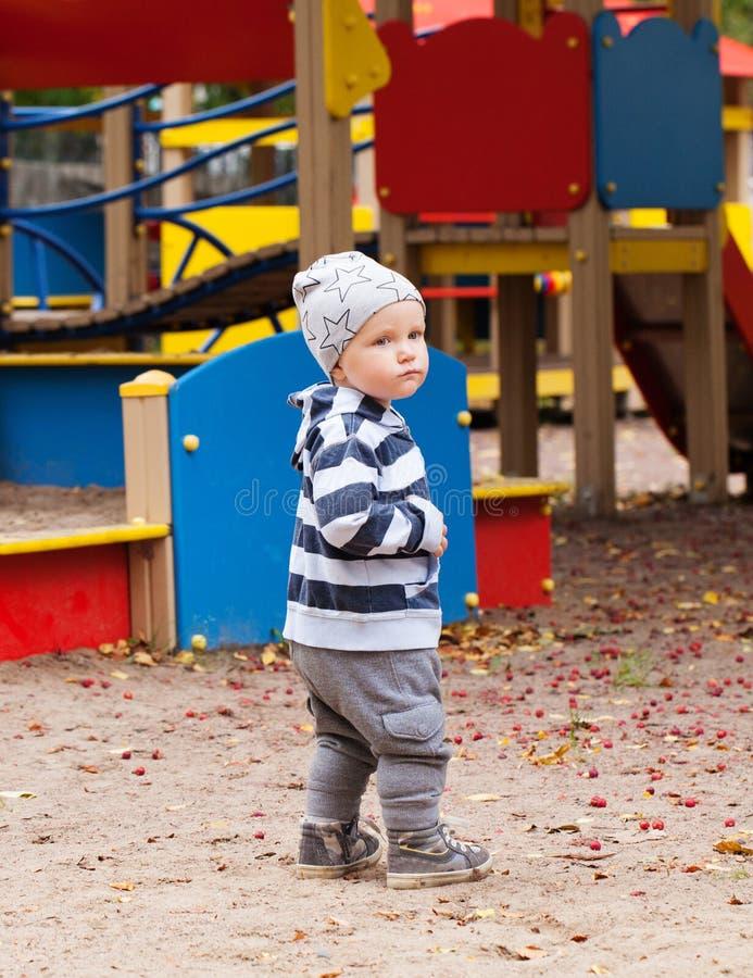 Ребёнок играя на спортивной площадке outdoors стоковое изображение rf