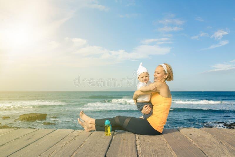 Ребёнок играя с матерью на пляже, летним днем стоковая фотография rf