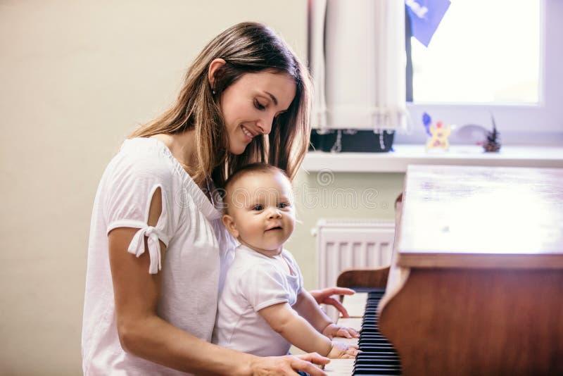 Ребёнок матери и малыша, играя рояль дома стоковое изображение rf