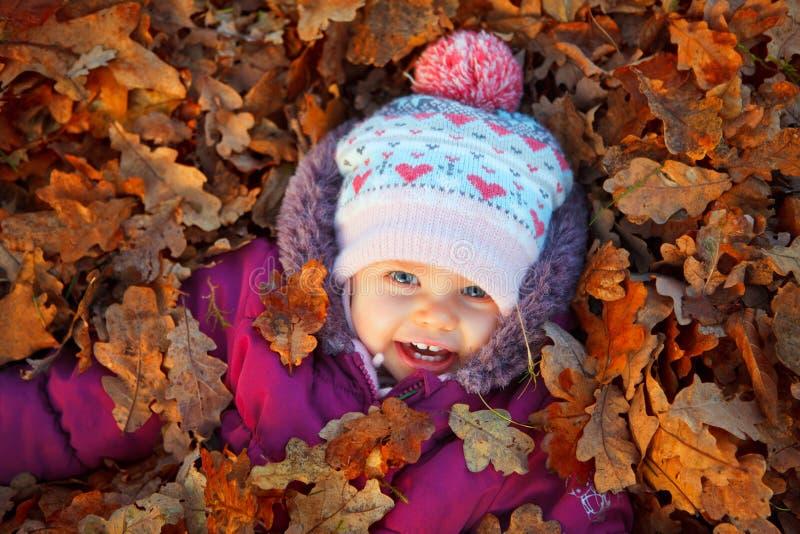 Ребёнок на листьях осени стоковые фото