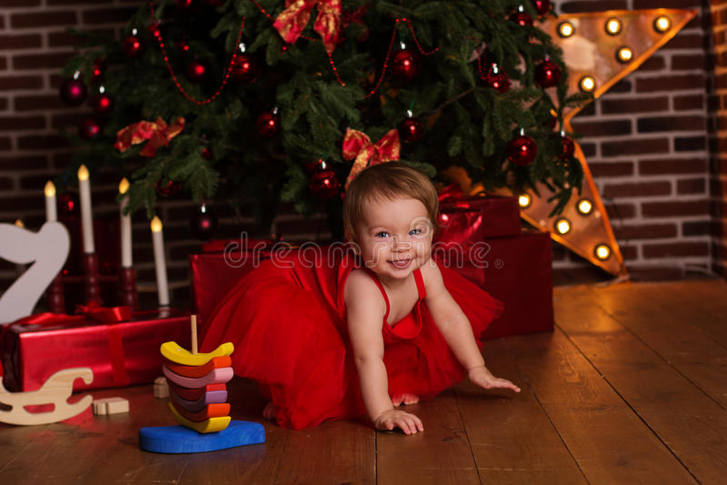Ребёнок около роскошной красной рождественской елки стоковое фото