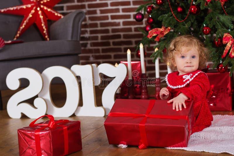 Ребёнок около роскошной красной рождественской елки стоковая фотография rf