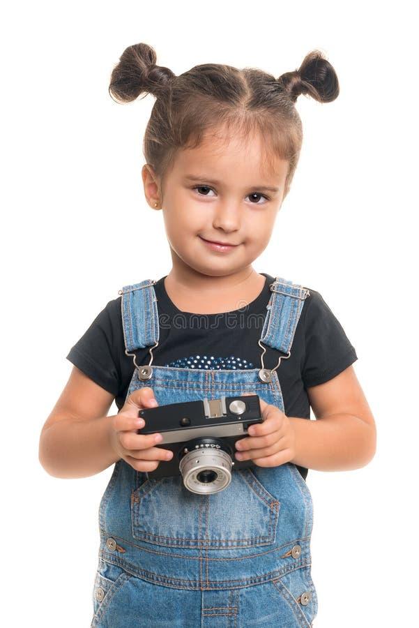 Ребёнок при винтажная камера представляя в студии изолировано стоковые изображения