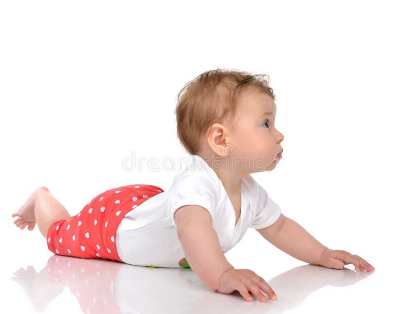 Ребёнок ребенка 4 месяцев младенческий лежа в красных брюках на поле стоковая фотография rf