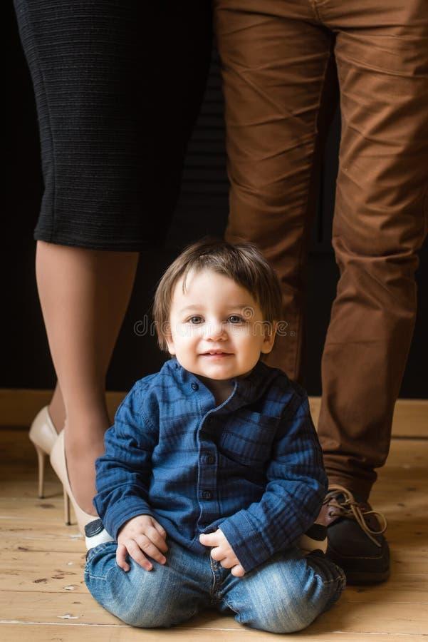 Ребёнок сидит и усмехается с родителями позади стоковые изображения rf