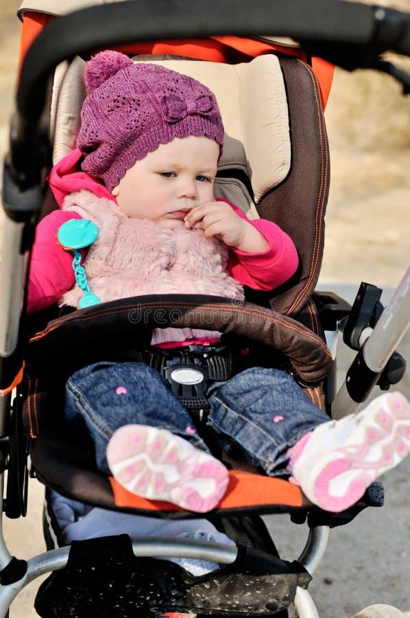 Ребёнок сидя в прогулочной коляске стоковые фотографии rf