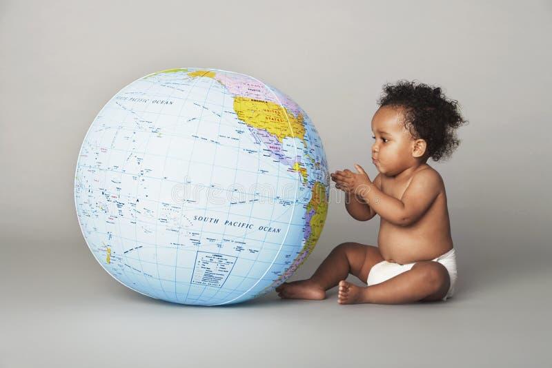 Ребёнок смотря раздувной глобус стоковые изображения