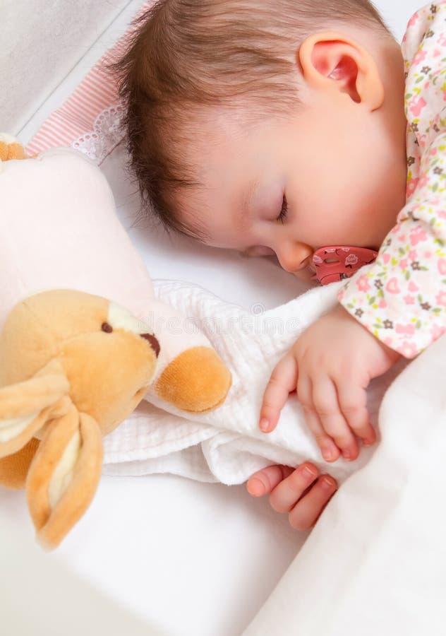 Ребёнок спать в кроватке с pacifier и игрушкой стоковые изображения