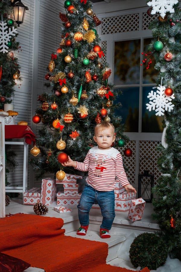 Ребёнок стоя около рождественской елки стоковая фотография