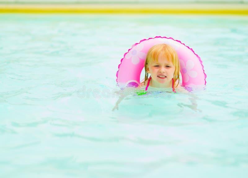 Ребёнок с заплыванием кольца заплыва в бассейне стоковые фото