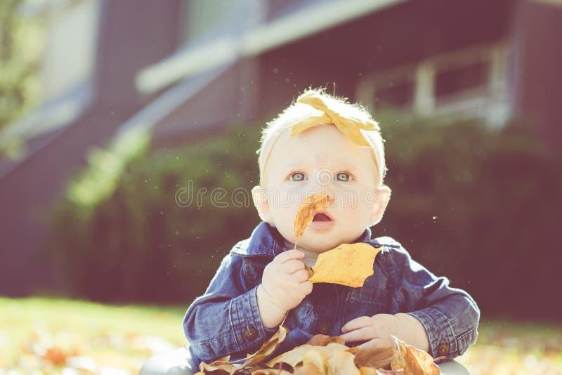 Ребёнок с смычком в голове играя с листьями на день падения стоковые фотографии rf