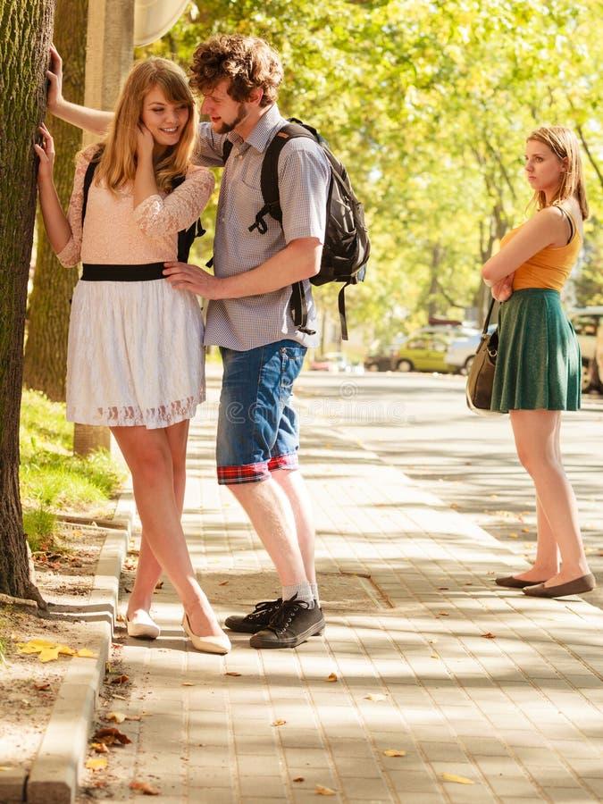 Ревнивая девушка смотря flirting пар внешних стоковое фото
