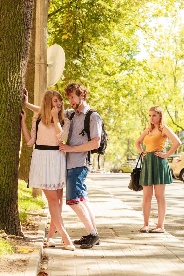 Ревнивая девушка смотря flirting пар на открытом воздухе стоковые изображения rf