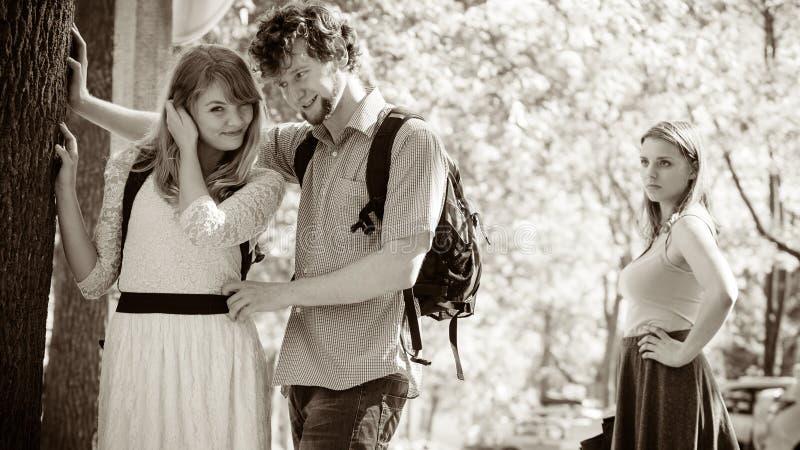 Ревнивая девушка смотря flirting пар внешних стоковые фотографии rf
