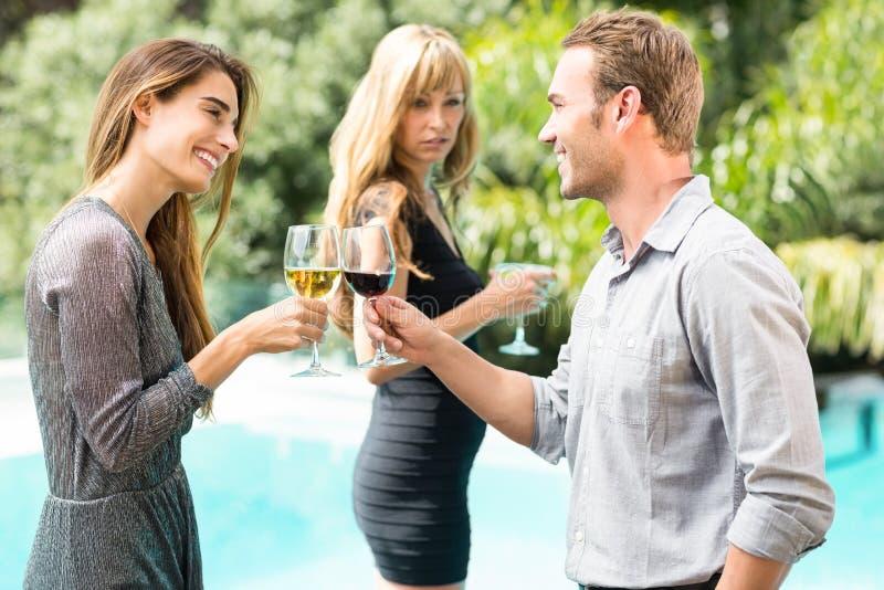 Ревнивая женщина смотря счастливых пар провозглашать вино стоковые изображения