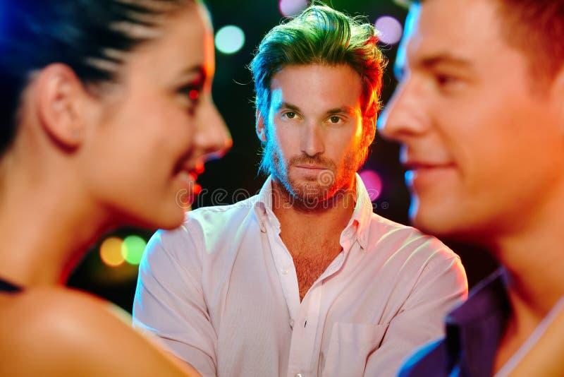 Ревнивый человек смотря flirting пар стоковое фото rf