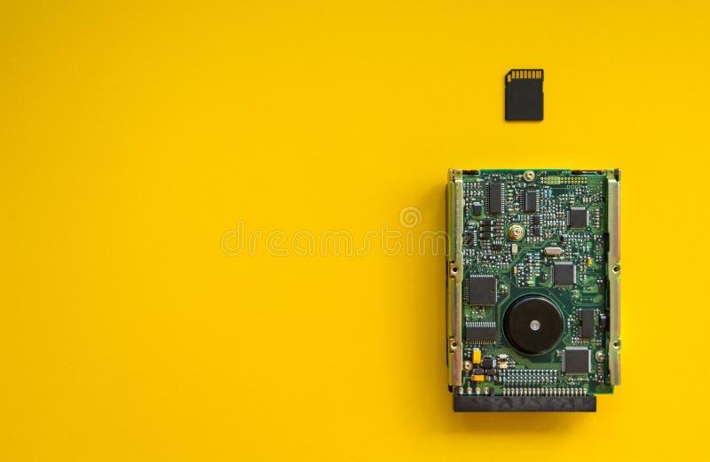Революция запоминающих устройств технологии на желтой предпосылке, концепции Жесткий диск и карта памяти стоковая фотография