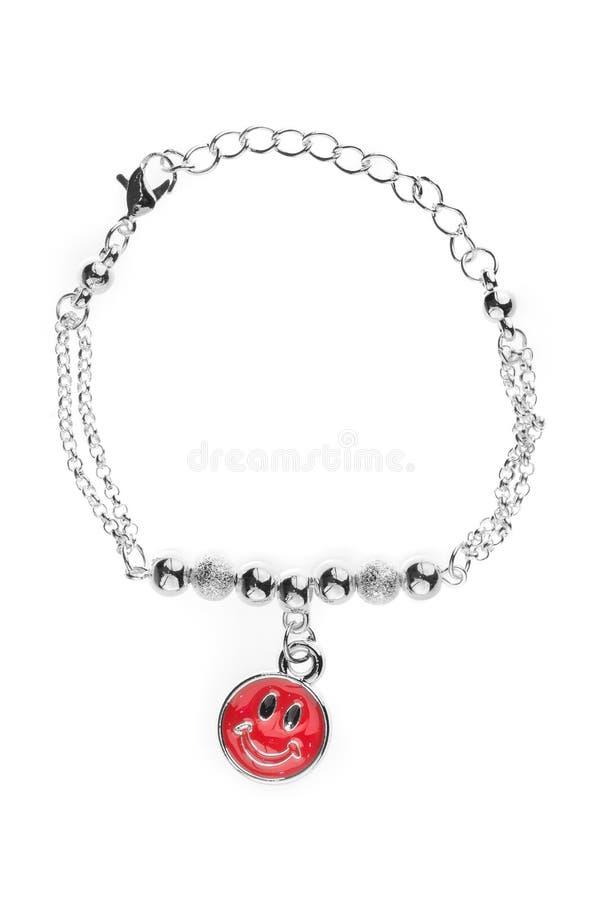Регулируемый серебряный браслет с жемчугами и серебряный круглый smiley шарика и больших красный на цепи, изолированной на белой  стоковая фотография