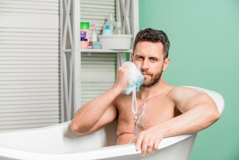 Регулярная ванна имеет большее настроение влияния чем физические упражнения Человек привлекательный с ванной взятия губки Личная  стоковые фотографии rf