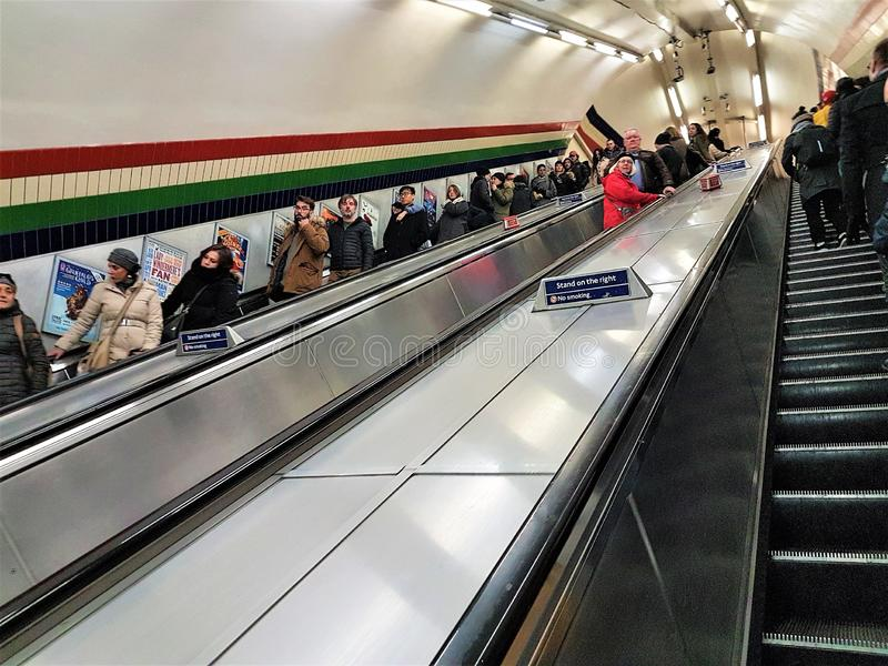 Регулярные пассажиры пригородных поездов путешествуют через подземные сети Londons на эскалаторах стоковая фотография