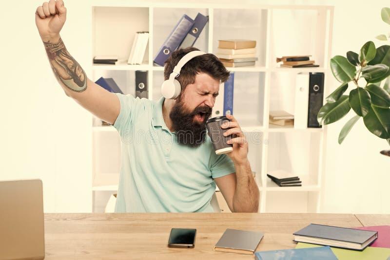 Регулярный день офиса Наушники парня человека бородатые сидят офис слушают музыка спеть песню Работник с кофейной чашкой начинает стоковая фотография