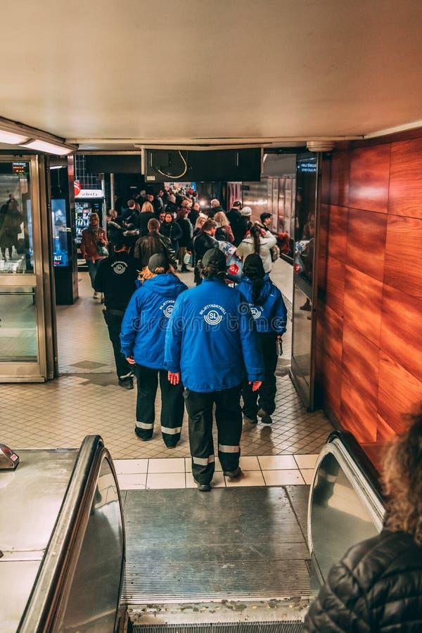 Регуляторы билета на там пути к платформе метро контролировать билеты пассажиров стоковая фотография rf