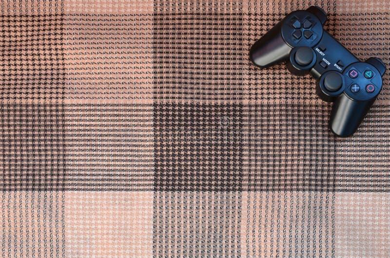 Регулятор видеоигры от консоли игры на checkered софе Беспроводное устройство для контролировать во время видеоигры стоковые фото
