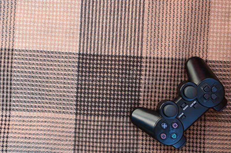 Регулятор видеоигры от консоли игры на checkered софе Беспроводное устройство для контролировать во время видеоигры стоковая фотография