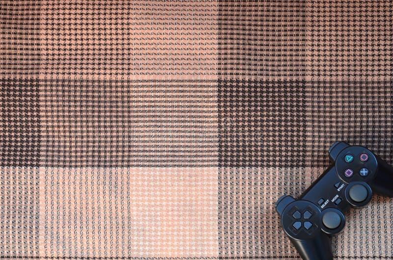 Регулятор видеоигры от консоли игры на checkered софе Беспроводное устройство для контролировать во время видеоигры стоковое фото