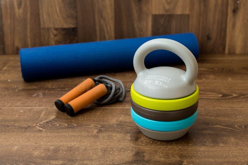 Регулируемое kettlebell, скача веревочка и циновка для fitnes на деревянной предпосылке Весы для тренировки фитнеса стоковое изображение